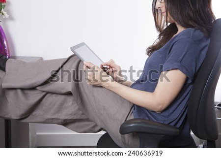 woman blue shirt sitting at black seat in office touching screen tablet - stock photo