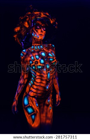 Woman blur with ultraviolet body art - stock photo