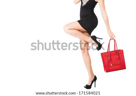 woman body in short black dress, high heel shoes hold in hand red handbag  - stock photo