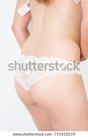 Woman body indoors in lingerie. Rear view