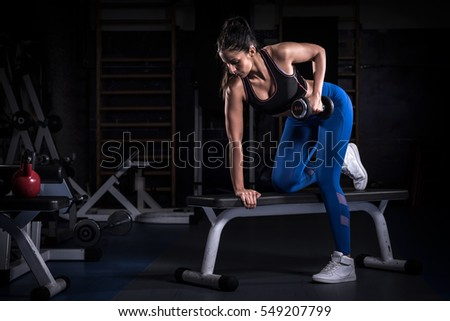 Woman bodybuilder in gym lifting dumbbells  on bench
