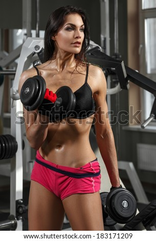 Woman bodybuilder training with dumbbell. - stock photo