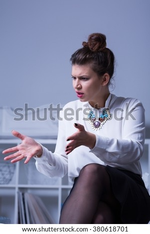 Woman boss, elegant and attractive sitting, gesticulating with grimace on face - stock photo
