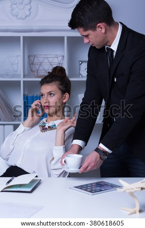 Woman boss with grimace on face holding cellphone and male secretary in suit with cup - stock photo