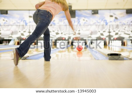 Woman bowling, rear view