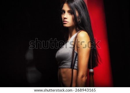 woman boxer near red punching bag over dark background - stock photo