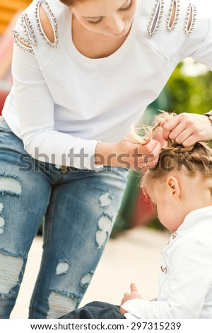 Woman braids pigtails to girl on the openair