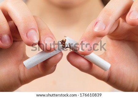 Woman breaking a cigarette, quit smoking concept, - stock photo