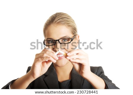 Woman breaking cigarette to stop smoking. - stock photo