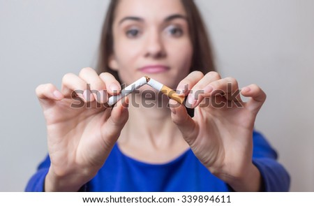 Woman breaks a cigarette - the concept of quitting - stock photo