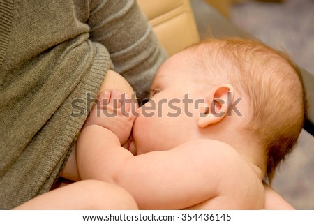 Woman breastfeeding her small baby, close-up.
