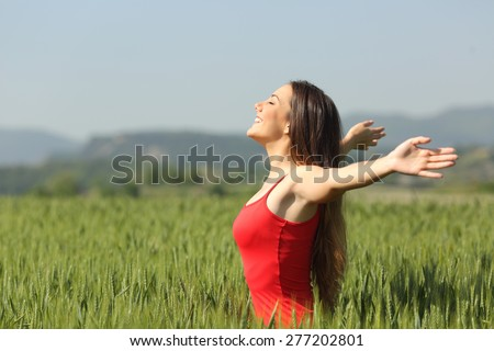 Woman breathing deep fresh air in a green wheat field wearing a red shirt - stock photo