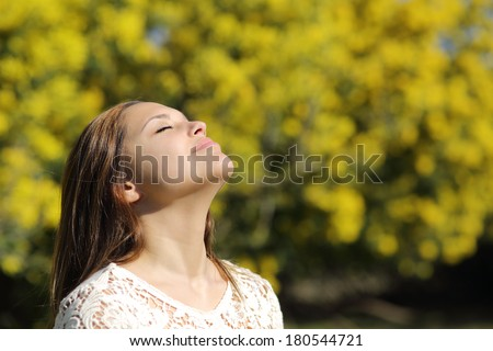 Woman breathing deep in spring or summer with a yellow background - stock photo