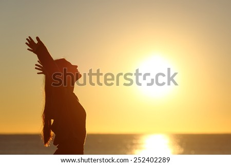 Woman breathing fresh air at sunset on the beach and raising arms - stock photo