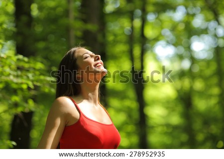 Woman breathing fresh air in a green forest in summer wearing a red shirt - stock photo