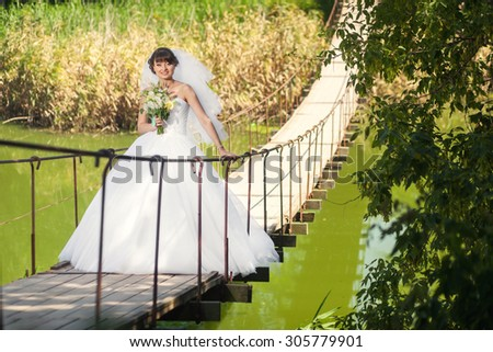 Woman bride standing on the bridge over the river
