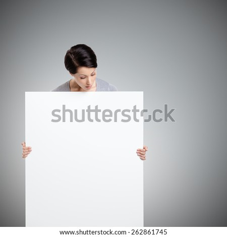 Woman brings a huge sheet of white cardboard, isolated on grey - stock photo