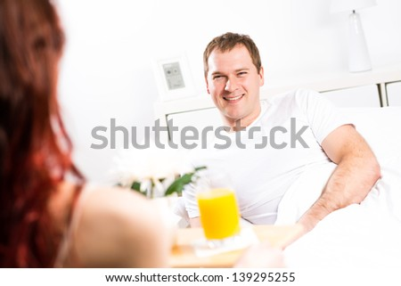 woman brought her boyfriend breakfast in bed, holding a tray of juice and breakfast - stock photo