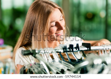 Woman browsing through clothes on a rack in a fashion store - stock photo