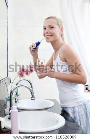 Woman brushes her teeth in bathroom - stock photo