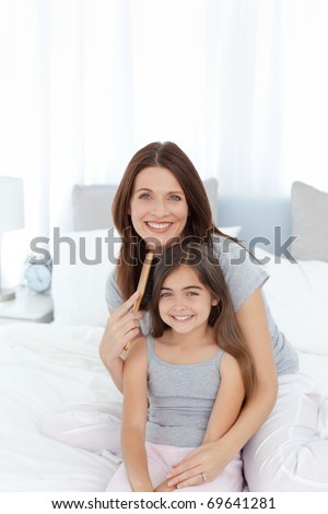 Woman brushing her daughter hair at home - stock photo