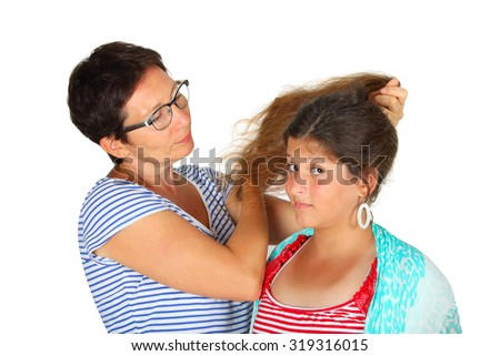 woman brushing her daughter's hair against a white background - stock photo