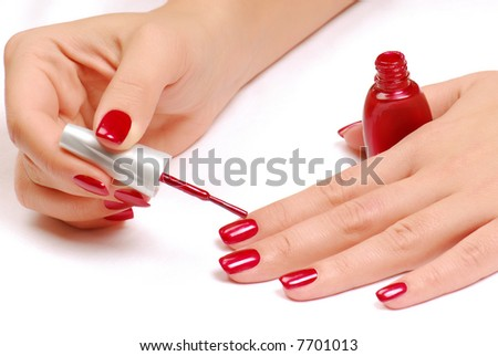 Woman brushing her nails in the red color