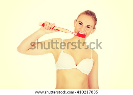 Woman brushing her teeth with huge toothbrush - stock photo