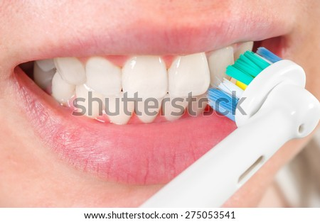 Woman brushing teeth with electric toothbrush, closeup - stock photo