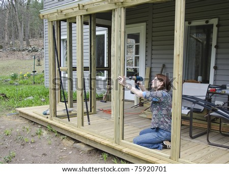 woman building screened porch - stock photo