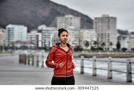 Woman busy taking a jog on the promenade along the ocean side with the city scape in the background beneath the mountain behind her - stock photo