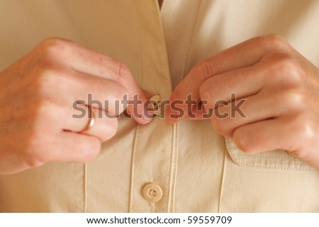 Woman buttoning her beige shirt - stock photo