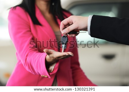Woman buying a car and salesman handling keys - stock photo