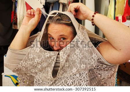 woman buying at market, empty price-tag on dress - stock photo