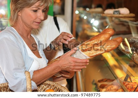 Woman buying bread - stock photo