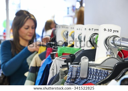 Woman Buying Children's Clothes In Charity Shop - stock photo