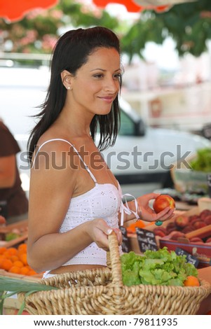 Woman buying fruit and vegetables at outdoors market - stock photo
