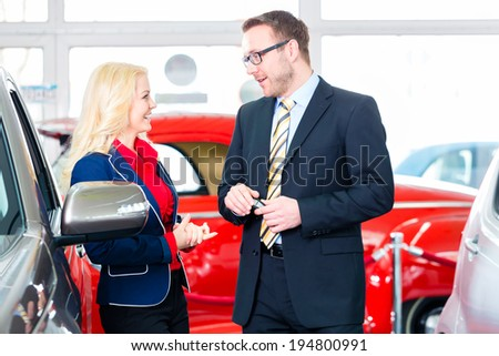 woman buying new car in auto dealership  - stock photo