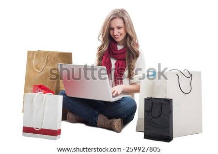 Woman buying online using laptop and sitting on the floor with shopping bags - stock photo