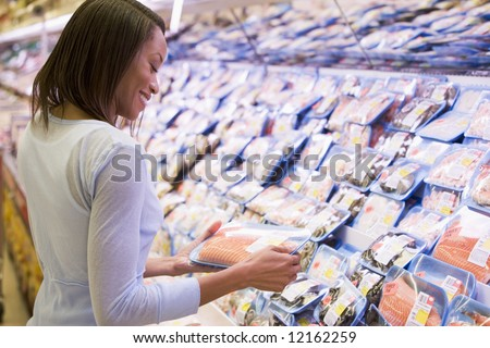 Woman buying pack of salmon in supermarket - stock photo