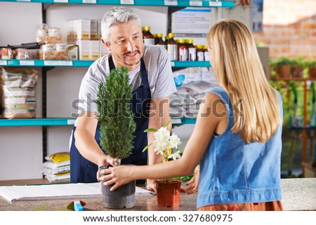 Woman buying plants in nursery and talking with salesman - stock photo
