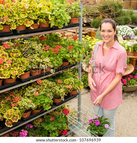 Woman buying potted flower in garden center with shopping basket