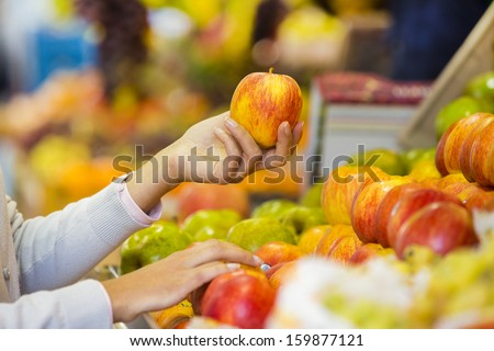 Woman buys fruits and vegetables at a market, apple - stock photo