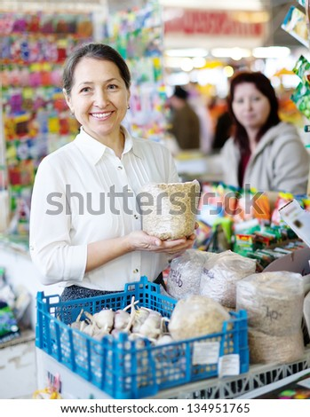 woman buys the seeds in bag on the market - stock photo