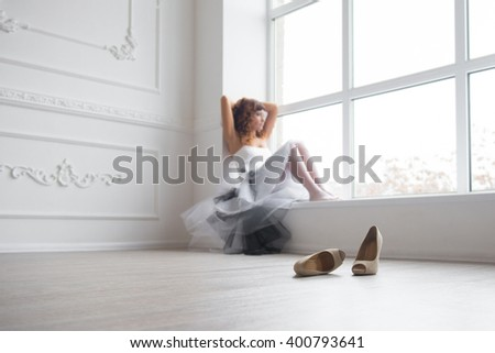 Woman by the window. Bride looking out the window, she waits for the groom. Beautiful bride in white wedding dress. elegant beautiful woman in white dress with creative hairstyle. shoes on the floor  - stock photo