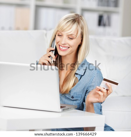 Woman calling and holding a credit card in front of her laptop