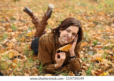woman calling by phone in autumn park - stock photo
