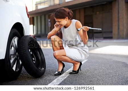 Woman calling for assistance with flat tire on car in the city - stock photo