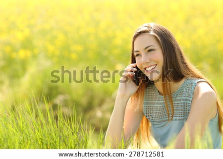 Woman calling on the mobile phone in a green field with yellow flowers - stock photo