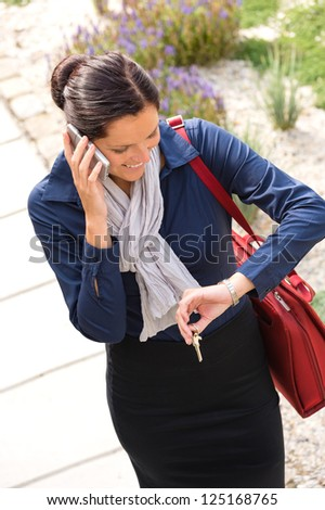 Woman calling rushing arriving home keys smart phone elegance business - stock photo